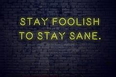 Citações inspiradores positivas no sinal de néon contra a estada da parede de tijolo insensata ficar são ilustração royalty free