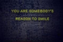 Cita inspiradora positiva en señal de neón contra la pared de ladrillo usted es razón de los somebodys para sonreír libre illustration