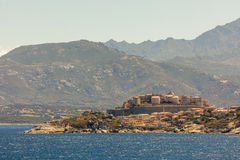 Citadel of Calvi in Corsica with mountains behind Stock Photography