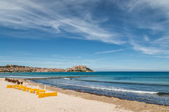 Citadel of Calvi with sunbeds lined up on beach in Corsica Stock Image