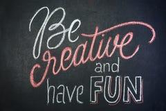 Citation - soyez créatif et ayez l'amusement sur le tableau noir manuscrit par des craies de couleur Photographie stock libre de droits