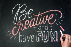 Citation - soyez créatif et ayez l'amusement sur le tableau noir manuscrit par des craies de couleur avec la main Photo libre de droits