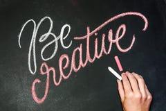 Citation - soyez créatif sur le tableau noir manuscrit par des craies de couleur avec la main Image stock