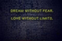 Citazione d'ispirazione positiva sull'insegna al neon contro il sogno del muro di mattoni senza amore di timore senza limiti fotografia stock libera da diritti