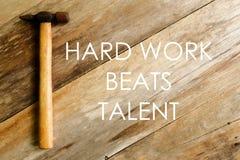 Citazioni ispiratrici e motivazionali Il duro lavoro batte il talento Martello su fondo di legno fotografia stock