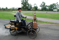 Cite de l'automobile, Mulhouse, France. This image presents a men driving one of the first car ever made by humans at the Cite de l`automobile in Mulhose, France Stock Photo