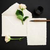 Citera skriftligt i kalligrafistil på pappers- kort med blommor, färgpulver och pennan på svart bakgrund Lekmanna- lägenhet, bäst Fotografering för Bildbyråer