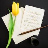 Citera skriftligt i kalligrafistil på pappers- kort med blommor, färgpulver och pennan på svart bakgrund Lekmanna- lägenhet, bäst Royaltyfri Foto
