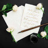 Citera skriftligt i kalligrafistil på pappers- kort med blommor, färgpulver och pennan på svart bakgrund Lekmanna- lägenhet, bäst Arkivfoton