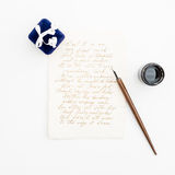 Citez écrit dans le style de calligraphie sur la carte de papier avec l'encre et le stylo sur le fond blanc Configuration plate,  Photo stock