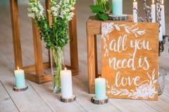 Citez tous que vous avez besoin est amour sur le panneau en bois de vintage avec des bougies et des fleurs sur le fond Images stock