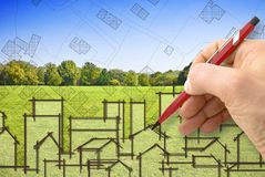 Cities and green spaces - concept image with architect drawing a residential district over a green mowed lawn with trees.  royalty free stock image