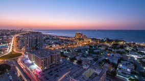 Citiscape of Ajman and Sharjah day to night timelapse from top stock photo