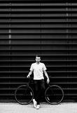 Citizen with fixed gear bike. Hipster young man in a white T-shirt with a bicycle. Male citizen with fixed gear bike in an urban environment Stock Photo