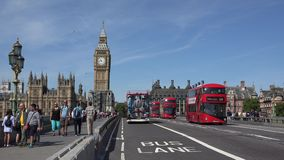 Citizens, commuters, tourists, red double decker buses and black retro taxi cabs on Westminster Bridge. Near the Big Ben of London city during a sunny quiet day stock video