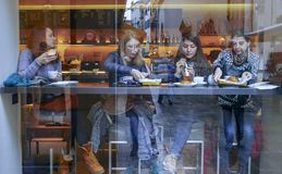 Citizens` reflections in a window of a bar royalty free stock image
