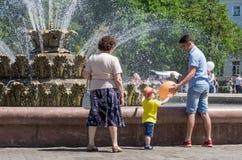 Citoyens sur une promenade en parc de ville près de la fontaine Un jeune homme renvoie un ballon à un petit garçon images stock