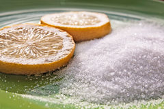 Citric acid and two slices of a lemon. On the green plate Royalty Free Stock Image