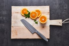 Citrinas frescas, fatias alaranjadas do meio corte na placa de corte com a faca no fundo de pedra escuro, configuração lisa foto de stock