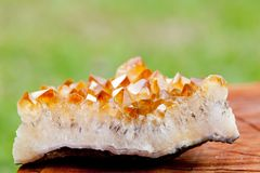 Citrine crystal cluster on wooden tree stump Stock Photo