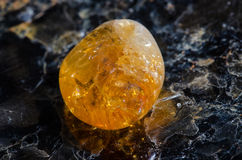 Citrine macro. Polished citrine crystal, illuminated from behind; on a slab of mica Stock Images