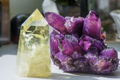 Citrine stone and amethyst. Yellow, clear crystal with dark, smokey color, smoky quartz with ornaments and rainbows in it. Amethyst is a violet variety of stock photography