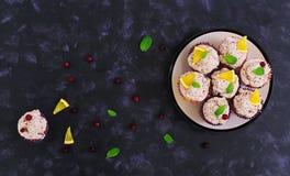 Citroen cupcakes met kersenroom Amerikaanse veenbes, muntbladeren Voedsel op een donkere achtergrond Hoogste mening Stock Foto