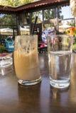 Citroen in een glas met een zachte sprankelende drank en een glas met frappe stock afbeeldingen