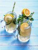 Citroen en cucucmber detox water in glaskruiken stock afbeeldingen