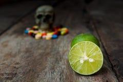 Citroen en menselijke schedel in de stapel van drugs Royalty-vrije Stock Afbeeldingen