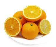 Citroen en sinaasappelen op een plaat Stock Afbeelding