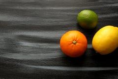 Citroen, kalk en bloedsinaasappel op zwarte raad Stock Foto