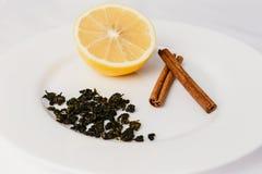 Citroen, kaneel en groene thee op een witte plaat Stock Afbeelding