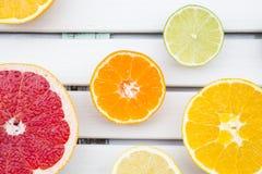 Citroen, mandarijn, oranje en roze grapefruit op wit hout Stock Foto