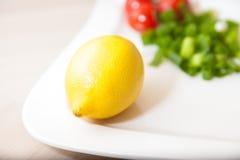 Citroen op een witte plaat met andere groenten Royalty-vrije Stock Foto