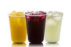 Citroen, Sinaasappel en druivesap met ijs binnen een paar plastieken op witte achtergrond stock foto's