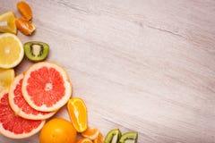 Citroen, sinaasappel, kiwi, grapefruit, mandarin op een houten oppervlakte regeling van gesneden fruit Hoogste mening met exempla Stock Afbeelding