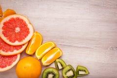 Citroen, sinaasappel, kiwi, grapefruit, mandarin op een houten oppervlakte regeling van gesneden fruit Hoogste mening met exempla Royalty-vrije Stock Fotografie