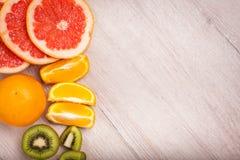Citroen, sinaasappel, kiwi, grapefruit, mandarin op een houten oppervlakte regeling van gesneden fruit Hoogste mening met exempla Stock Foto