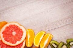 Citroen, sinaasappel, kiwi, grapefruit, mandarin op een houten oppervlakte regeling van gesneden fruit Hoogste mening met exempla Royalty-vrije Stock Afbeelding