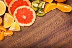Citroen, sinaasappel, kiwi, grapefruit, mandarin op een houten oppervlakte regeling van gesneden fruit Hoogste mening met exempla Royalty-vrije Stock Foto's
