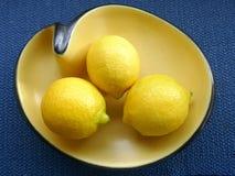 3 citroenen in een oude gele ceramische kom, niervorm, jaren '50 - jaren '60, tegen blauwe achtergrond royalty-vrije stock afbeeldingen