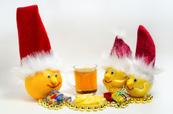 Citroenen en grapefruit in Kerstmishoeden en thee met citroen Stock Afbeeldingen