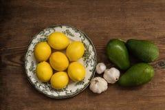 Citroenen op witte plaat met knoflook en avocado's over rustieke achtergrond Royalty-vrije Stock Afbeeldingen