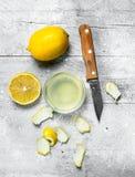 Citroensapkom met de schil van een citroen en een mes royalty-vrije stock afbeelding