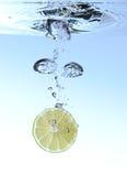 Citron éclaboussant dans l'eau Photographie stock libre de droits