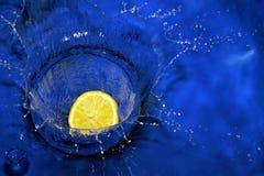 Citron éclaboussant l'eau bleue Image libre de droits