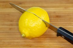 Citron étant découpé en tranches dans la moitié sur une planche à découper sur une table de cuisine image stock
