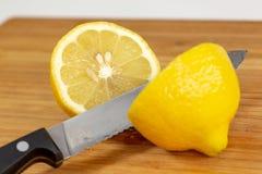 Citron étant découpé en tranches dans la moitié sur une planche à découper sur une table de cuisine photo libre de droits
