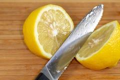 Citron étant découpé en tranches dans la moitié sur une planche à découper sur une table de cuisine photographie stock
